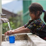 Young Girl Washing Hands Under a Tap - Executive Enterprise Giving Back to great causes